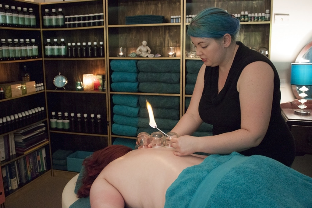 Female therapist completing Russian Cupping on patient