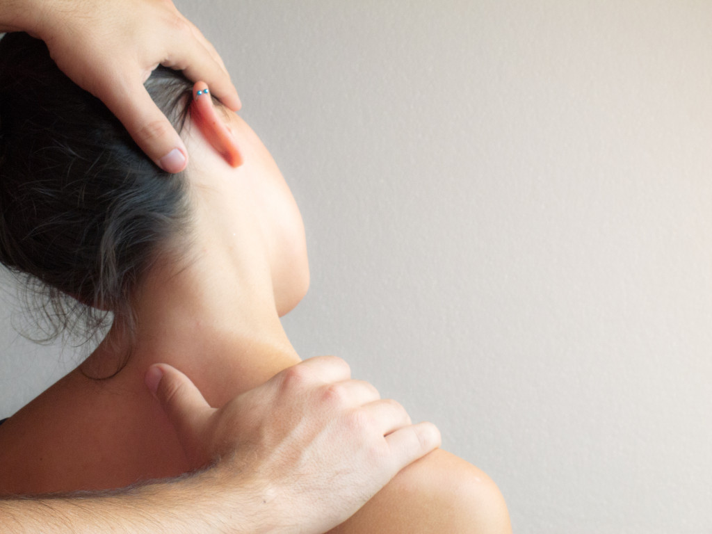 Two hands massaging and stretching female neck